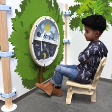 Op deze afbeelding ziet u een kind op de Buxus Lounge chair wood uit de kindermeubel collectie Buxus