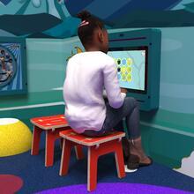 Op deze afbeelding ziet u een kind op de Buxus Stool red uit de kindermeubel collectie Buxus